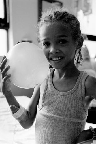 <p>&quot;This girl is in the same room as the previous photo. I spotted her, playing with a balloon with corn rows in her hair. When I started taking her picture, she put the ball down and started to pose. I communicated to her -- and her mom who was on the left--to keep playing and just keep doing what she's doing. So this is the result.&quot;</p>
