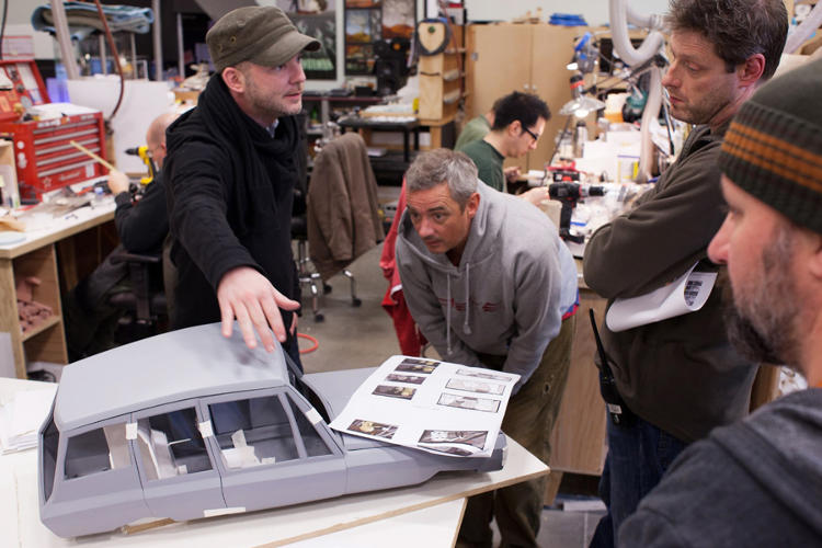 <p>Directors Chris Butler and Sam Fell discuss a car sculpture with Director of Photography Tristan Oliver.</p>