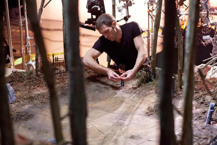 <p>Travis Knight on the set, in a forest made of cardboard trees, with Norman. One second of stop-motion animation is created from 24 individually composed frames.</p>