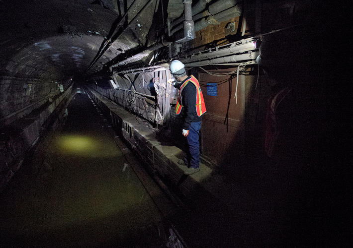 <p>MTA employees look down the L Train tunnel. Photo: Patrick Cashin.</p>