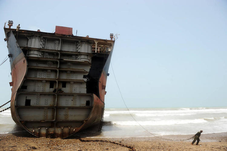 <p>Here, a Pakistani worker pulls on a wire that he'll connect to a thick chain used for peeling away part of the outer structure of a lodged vessel in one of the 127 ship-breaking plots in Geddani on July 10, 2012.</p>