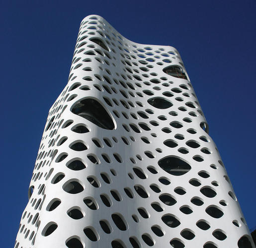 <p>Built two years ago, Reiser + Umemoto's 0-14 Tower in Dubai has a perforated concrete shell that protects inhabitants from the penetrating desert sun and helps ventilate the building. The architects were able to build the shell--absent any vertical columns and horizontal floor lines--by packing plastic forms into densely packed bundles of reinforced steel before casting the concrete.</p>
