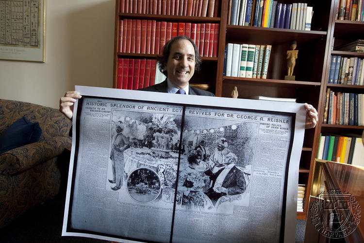 <p>Harvard Egyptology professor Peter Der Manuelian shows off an old newspaper heralding archeologist George Reisners's Giza discoveries.</p>