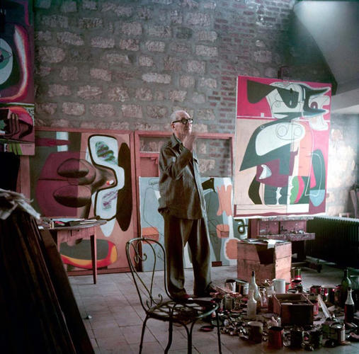 <p>Le Corbusier stands in his Paris apartment, surrounded by paintings, in 1953. This and other rare color images shot by Willy Rizzo are on view in an exhibition this month.</p>