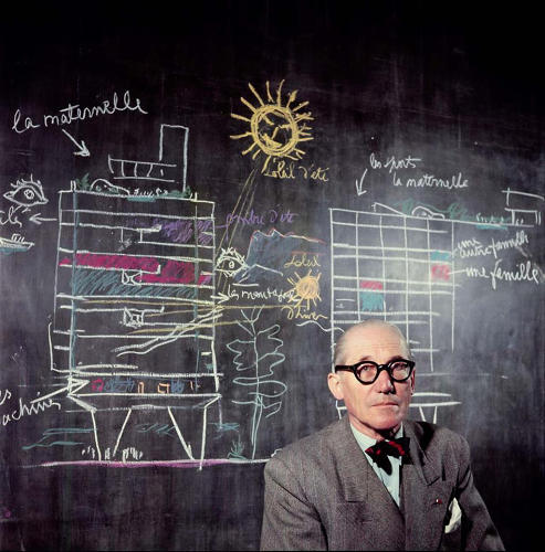 <p>Here, Le Corbusier sits in front of a section diagram of his Unité d'Habitation, labeled with color chalk.</p>