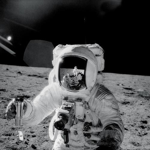 <p><strong>Astronaut Mirror</strong><br /> Apollo 12 astronaut Alan Bean holds a special environmental sample container filled with lunar soil collected during his sojourn on the lunar surface. A Hasselblad camera is mounted on the chest of his spacesuit. Pete Conrad, who took this image, is reflected in Bean's helmet visor, November 20, 1969.</p>