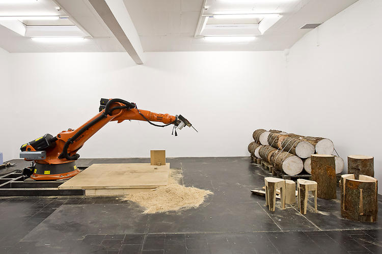 <p>The work itself is performed by an industrial robot wielding an electric chainsaw.</p>