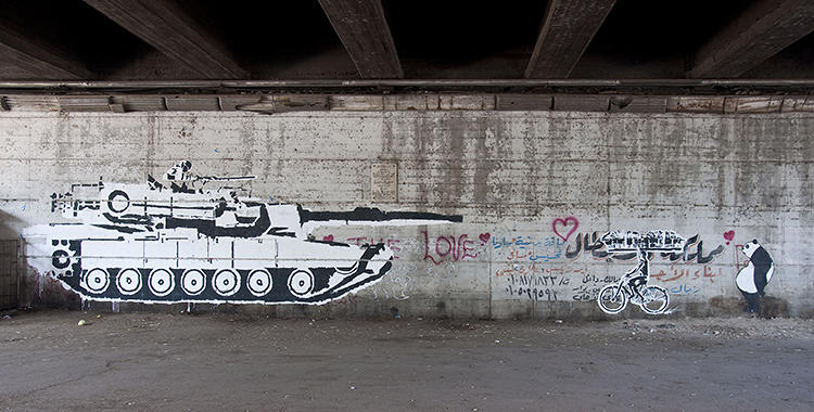 <p>&quot;Ganzeer and a team of his friends created 'The Tank vs. Biker' during 'Mad Graffiti Weekend' in May 2011. The mural depicts a hypothetical yet ironic duel between a military tank and a boy on a bicycle carrying a basket of bread. The unmatched opponents are frozen in motion on a huge wall under a bridge in Zamalek alluding to the absurd reality of the military attacking its own citizens. The 'bread boy' is a symbol of the revolution with its slogan 'Bread, Freedom and social justice.'&quot;</p>