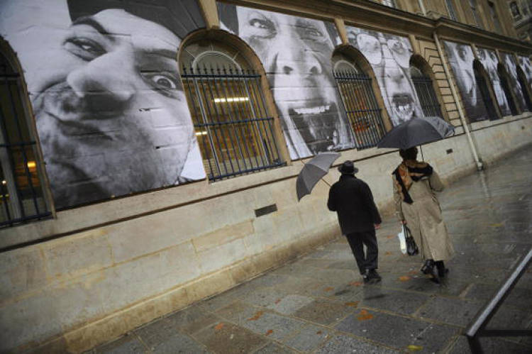 A series of portraits of Israeli and Palestinian faces. First displayed along the barrier separating Israel from the Palestinian Territories in 2007, these images later moved to walls in other cities, including Paris, shown here.