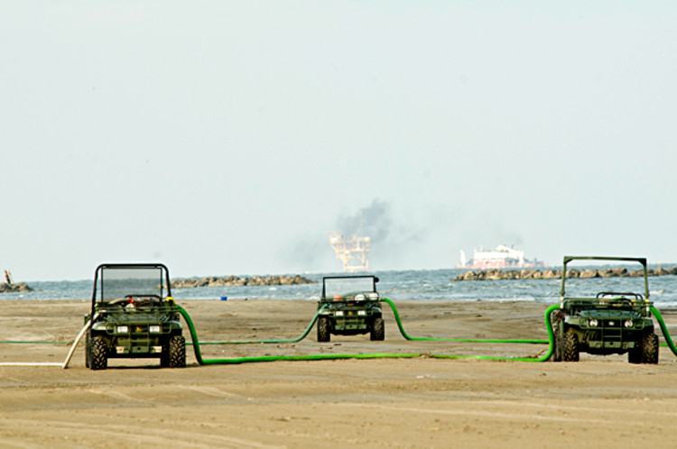 Mobile pumps supply water from the Gulf of Mexico to fill miles of boom that line the Grand Isle beach.