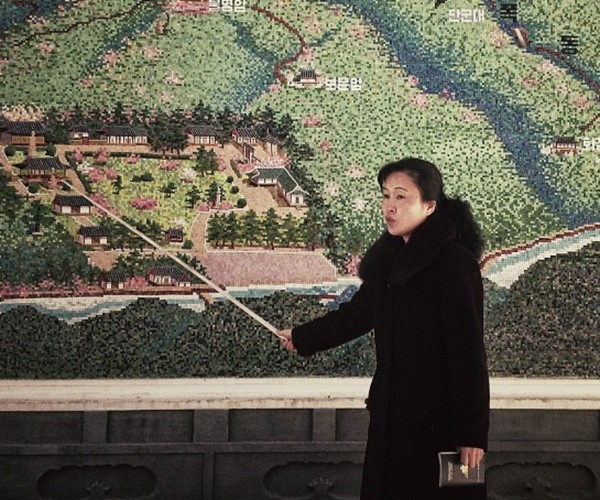 <p>A North Korean guide uses a pointer at the start of a tour of an historic site.</p>