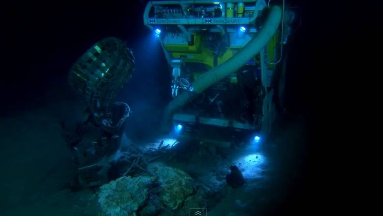 <p>A Bezos Expeditions remotely operated submersible works to clear silt from a piece of an Apollo rocket engine.</p>