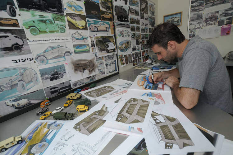 <p>Plasan Chief Designer Nir Kahn works on sketches.</p>