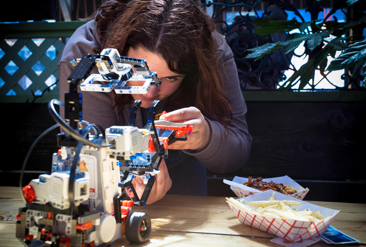 <p>Autodesk's Sherry Caywood puts the finishing touches on the team's robot, modeled after distracted San Francisco techies.</p>