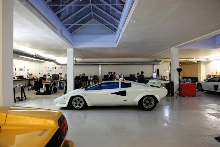 <p>A series of diminutive electric cars lines one wall. Desks, packing boxes, prototypes, and sports cars compete for attention in the all-white space. The garage also houses a 3-D printer, a laser cutter, 1980s arcade games, a workshop, and a roomful of vintage synthesizers and turntables.</p>
