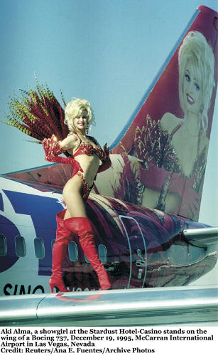 <p>Vegas showgirl Aki Alma stands on the wing of a Boeing 737, with her 37-foot portrait painted on the plane's tail. Part of the Western Pacific Airline's &quot;AirLogo&quot; program in the mid-1990s, the plane was advertising the Stardust Hotel-Casino.</p>