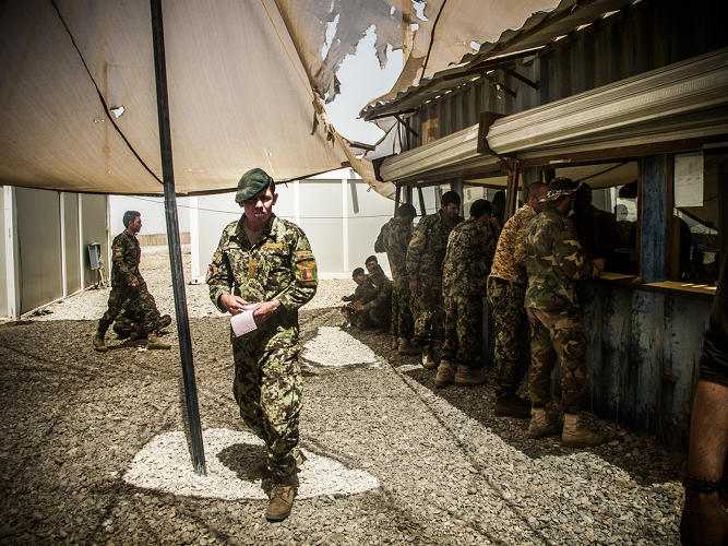 <p>A soldier of the Afghan National Army leaves the bank at Camp Garmsir after collecting his pay.</p>