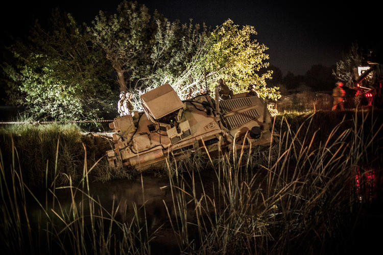 <p>Helmand's narrow roads are a challenge for the U.S. military's armored trucks, which occasionally slide off canal embankments. Such was the case in this accident, near Marjah, in Helmand Province. The overturned vehicle held the convoy up for half a night as they tried to extract it.</p>