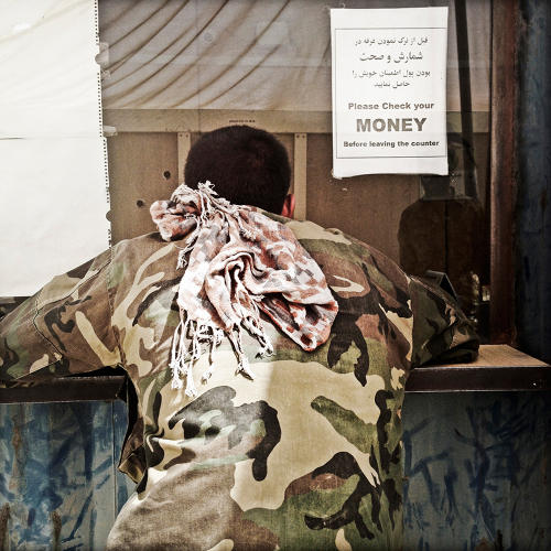 <p>An Afghan National Army soldier collects his pay at Camp Garmsir's on-base bank.</p>