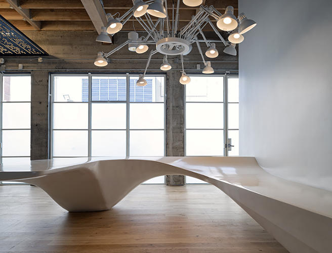 <p>The Giant Pixel founders shared two different design inspirations with the O+A team: the look of Charles and Ray Eames's workshop and <em>The Jetsons</em>. The latter inspired the curvy, concrete receptionist desk seen here.</p>