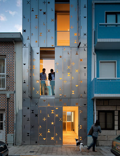"<p>This 760-square-foot gem of an urban dwelling features a stainless steel-paneled façade with folding metal shutters. Whimsical cutouts of ""siglas poveiras,"" a ""proto-writing"" system of communication used in Portugal, bring in daylight to the clean, modernist interiors without sacrificing privacy.</p>"
