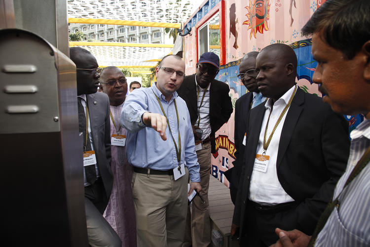 <p>Reinvent the Toilet Fair participants interact with Eram Scientific Solutions's self-cleaning communal toilet prototype, which features automatic sterilization after each use and incorporates multiple revenue generation options.</p>