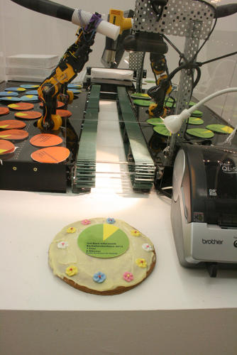 <p>Last November, Rüst debuted the Pie Bot in a gallery space in Switzerland. After gallery attendees chose which technology company's gender pie chart they wanted to print, the robot would place a pie on a conveyer belt and use a heat gun to make the chocolate topping sticky.</p>