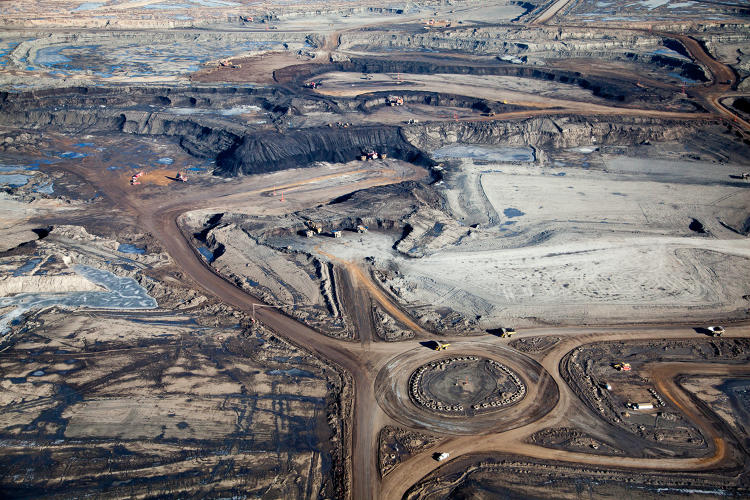 <p>Excavating bitumen at the Syncrude Mildred Lake mining site. Giant tires line traffic circle.</p>