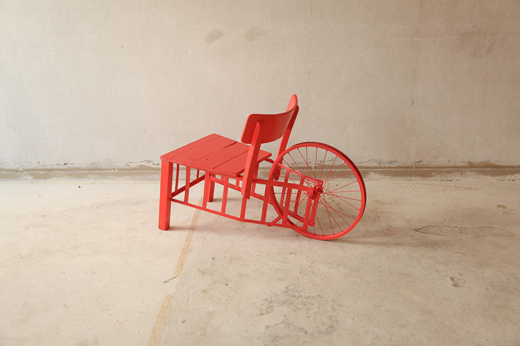 <p>There's a table with a tennis racket cross beam, a chair made from a bicycle wheel, and a desk fabricated from plastic crates found on the beach.</p>