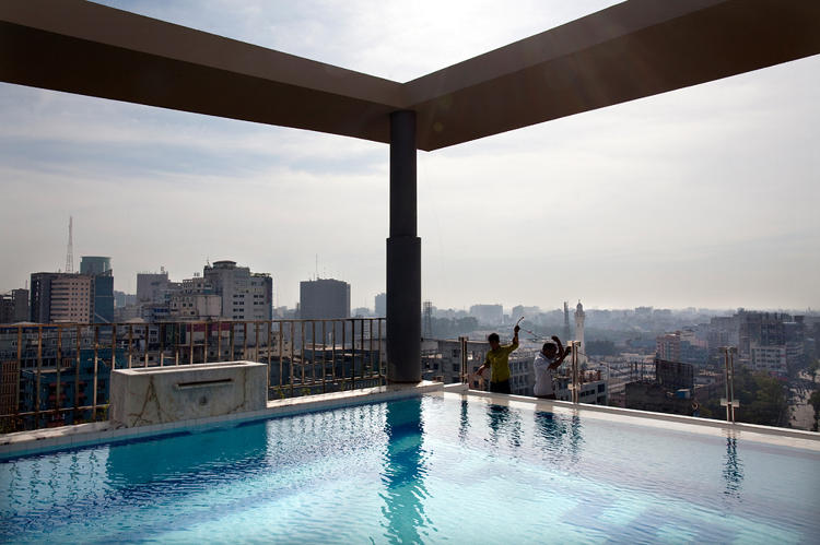 <p>Construction workers at the end of a hotel's infinity pool. &quot;These are low-cost workers in Bangladesh. They're standing on a really small ledge on the 10th floor. You or I would have fallen down. They build these beautiful pools, but not for themselves.&quot;</p>