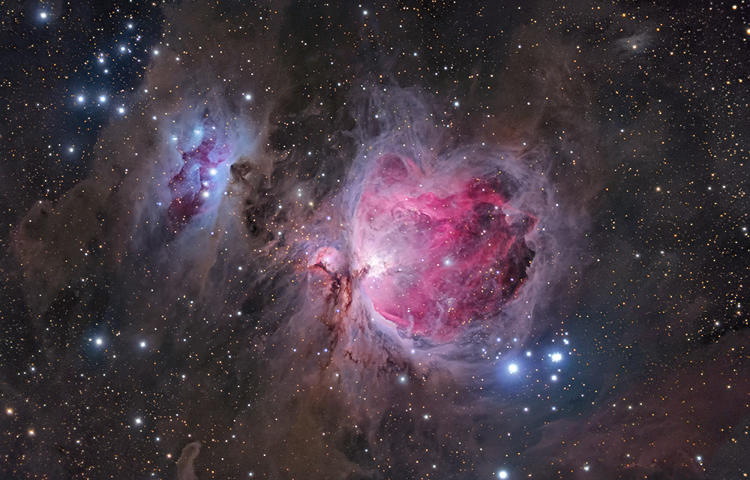 <p>In this view of M42, more commonly known as the Orion Nebula, the photographer has emphasized the delicate veils of dust surrounding the more familiar gleaming heart of the nebula. The image highlights the structure of the object, giving a sense of vast cavities filled with pink hydrogen gas and the blue haze of reflected starlight.</p>