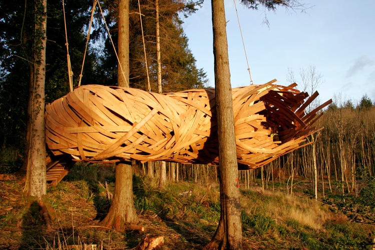 <p>This cocoon, made of cedar strips in a whimsical monocoque structure, weaves through the trees of a forest park. Visitors can curl up inside its undulating form.</p>