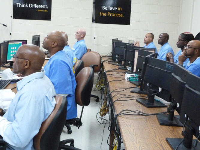 <p>Marcus Phillips, the CTO and Head of Instruction at Hack Reactor, taught the inmates via a Google Hangout that was projected onto a screen in front of the class. Two volunteers from Hack Reactor, including cofounder Shawn Drost, were in the room to provide personalized instruction.</p>