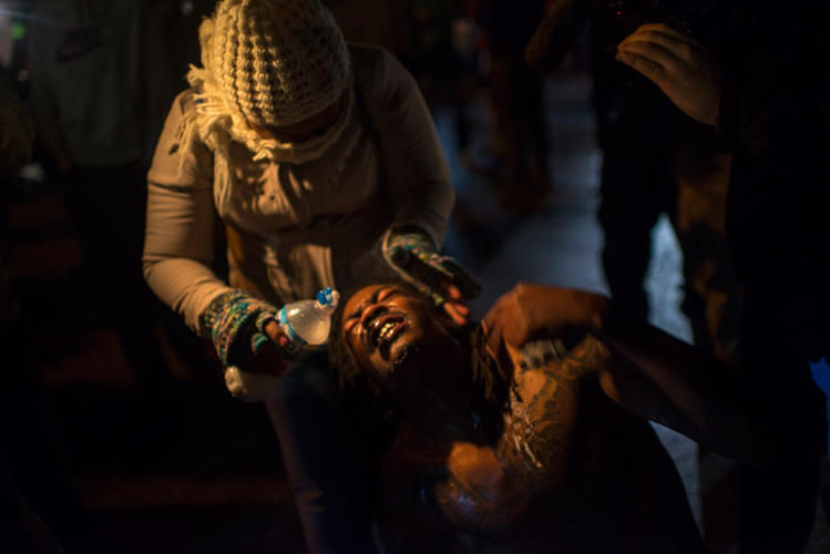 <p>Among the eight <a href=&quot;http://fineacts.co/postcardsfromferguson#ferguson-street&quot; target=&quot;_blank&quot;>Postcards from Ferguson</a> images: a woman being doused with water after getting pepper-sprayed by the police, small children walking by a line of police in the street, and a police car completely shrouded in tear gas.</p>