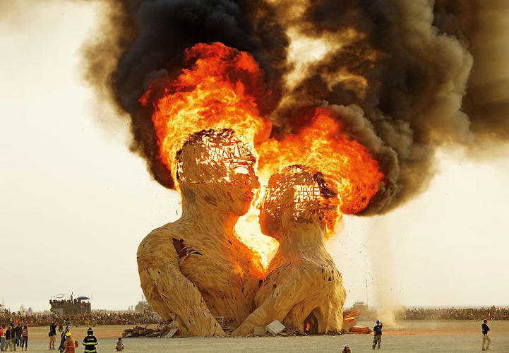 <p>Artists: Kevan Christiaens, Kelsey Owens, Bill Tubman, Joe Olivier, Matt Schultz, and the Pier Group<br /> Embrace, a massive wooden sculpture 70 feet tall, burns at dawn. The work symbolizes the nature of human relationships, and was built to burn.</p>