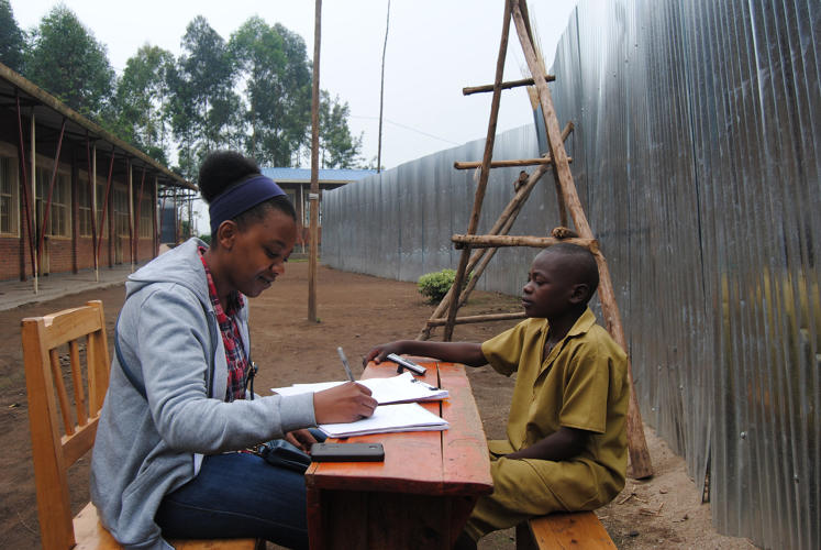 <p>Here, one of them, Marie Amelie Ntigulirwa interviews a student at the Mubuga School as part of research on the impact of infrastructure design on education</p>