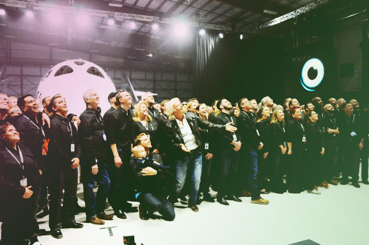 <p>Branson stands in front of dozens of Virgin Galactic employees for a team photo.</p>