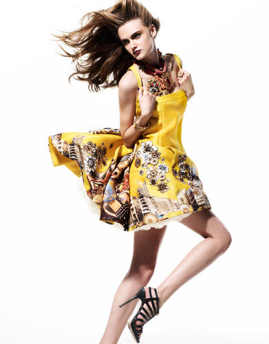 <p>A model wears a yellow dress adorned with collage by Dutch artist Tim Roeloffs for the Versace fall/winter 2008 women's ready-to-wear collection.</p>