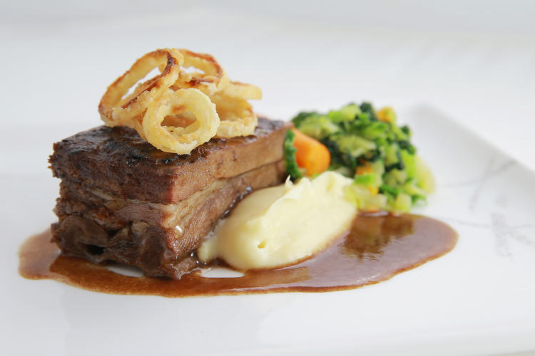 <p>Braised beef short rib with a red wine jus, parsnip puree, and crispy shallots—Cathay Pacific</p>