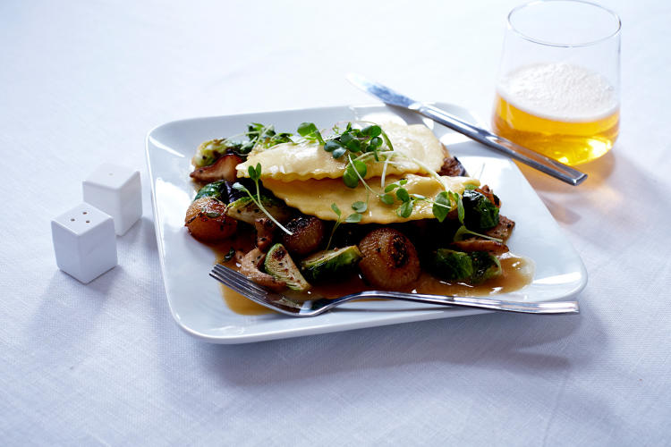 <p>Truffle and potato ravioli with honey-roasted forest mushrooms and parmesan broth—Delta</p>