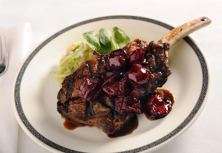 <p>Grilled veal chop with leek soubise and cherry compote— Singapore Airlines</p>