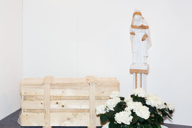 <p>Wrapped Madonna (a wrapped up statue next to a wooden box)</p>