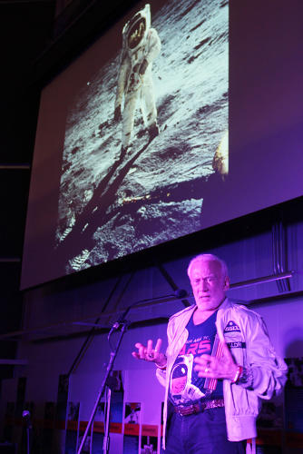 <p>regales the crowd with tales from his lunar voyage.</p>