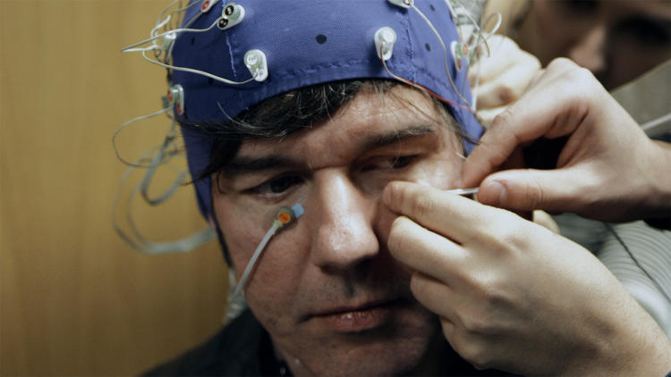 <p>Neuroscientists ran preliminary tests to assess Sagmeister's well-being prior to undergoing three experimental trials designed to make him happier. Shown here, an EEG test is underway.</p>
