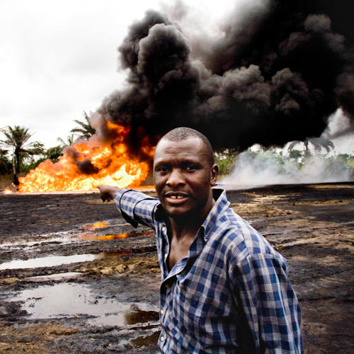 <p>In the Ogoniland village of Kpean, an oil wellhead that had been leaking for weeks has turned into a raging inferno. The local youths keep watch, waiting for Shell to come and put the fire out. This is an environmental disaster for the local people, as it effects their crops, their water, and their air.</p>  <p>Even though Shell has not been allowed to pump oil from its 125 wells in Ogoniland since 1993, they sill have wells that are leaking and often unattended or maintained. This lack of action, which pollutes the lands and forces farmers and fishermen out of work, makes relations between the local communities and Shell very fractious. This Shell oil well is more than 30 years old, and this scenerio is typical of the kinds of ongoing problems with the oil works of the Niger Delta.</p>