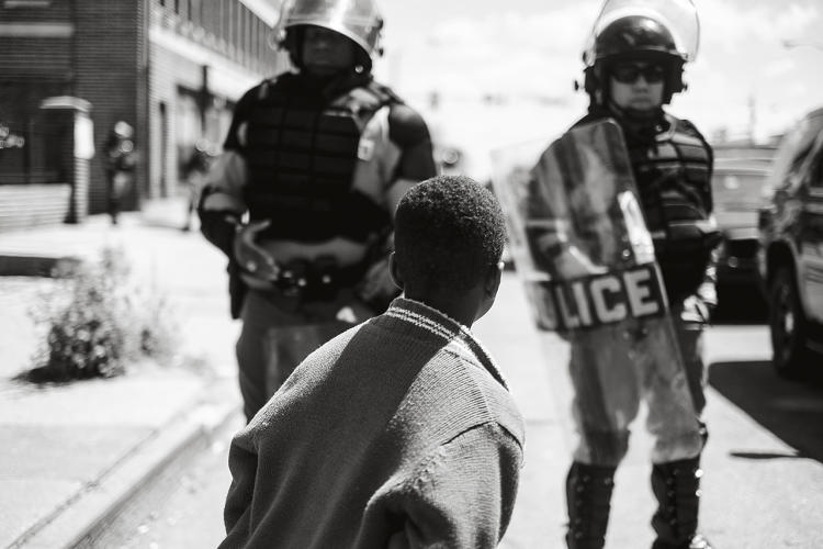 <p>Young boy standing in front of police officers at a blockade, North Avenue, West Baltimore, April 28, 2015. Photo: Devin Allen.</p>
