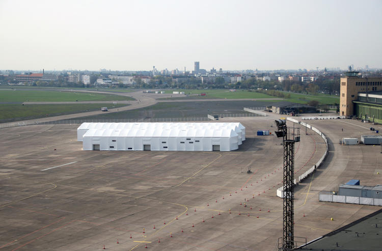 <p>At Berlin's Tempelhof airport, refugees were housed inside hangars. Gorenflos Architekten designed a reconfigurable structure to create social space.</p>