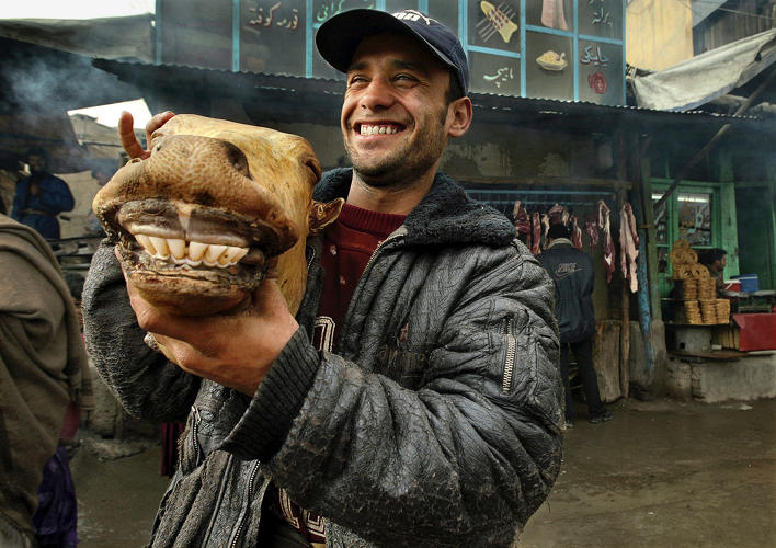 <p>An Afghan man shows off <strong>a cow's head</strong> that he is selling in the bazaar in Kabul, Afghanistan.</p>