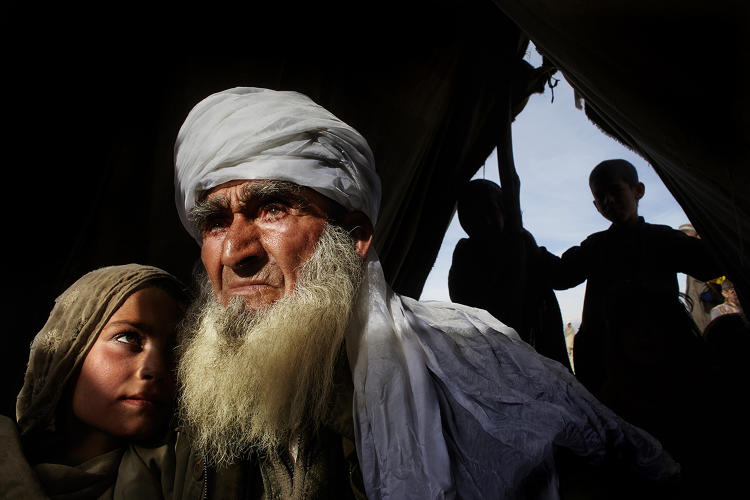 <p>An <strong>elderly man</strong> holds his granddaughter at a refugee camp after they fled their village, bombed by U.S. and NATO forces.</p>