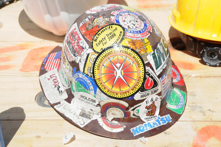 <p>A hard hat adorned with years of stickers, including a Department of Public Works logo.</p>